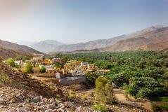 Een ver dorp met zijn oase en palmdataaanplanting in Oma stock afbeeldingen