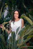Een verbazende en gelukkige jonge dame in het tropische bos de vrouw in een witte kleding op verse en exotische groene bladerenac royalty-vrije stock foto