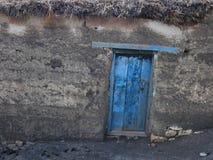 Een verdraaide blauwe houten deur op een oude grijze steenmuur Stock Fotografie