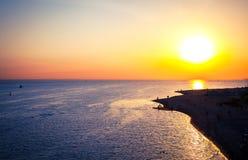 Een verdraaiende lijn van overzeese kust bij zonsondergang als achtergrond Stock Afbeelding
