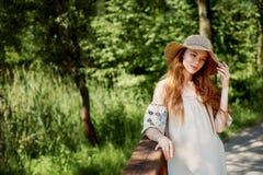 Een verfijnd roodharig meisje in een eenvoudige linnenkleding, in een licht breed-brimmed hoed Model kijk Natuurlijke Schoonheid royalty-vrije stock foto