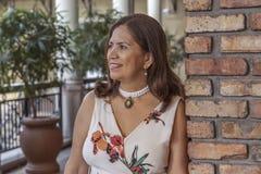 Een verfijnde Latijnse rijpe vrouw leunt op een bakstenen muur weg kijkend stock foto's