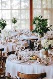 Een verfraaide rustieke huwelijkslijst met een wit die tafelkleed van porseleinplaten met glazen, met bloemen wordt verfraaid met royalty-vrije stock foto
