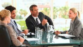 Een vergadering tussen vier bedrijfsmensen stock video