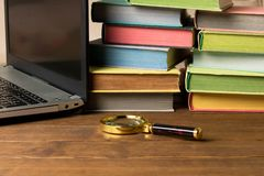 Een vergrootglas, een stapel boeken en laptop op een houten lijst Het concept informatieonderzoek op Internet en de boeken stock foto
