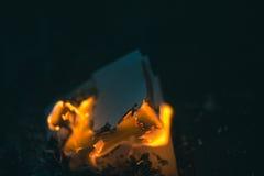 Een verkoold stuk van document op een donker Ijzer als achtergrond stock foto