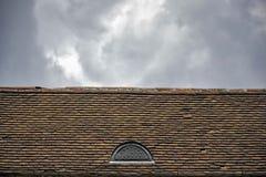 Een verlagings oud dak maakte van terracottategels tegen een bewolkte hemelachtergrond, architecturale details van een oud gebouw royalty-vrije stock foto's
