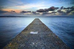 Een verlaten pier die in het overzees wordt uitgerekt. Stock Foto
