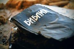 In een verlaten plaats ligt een gebrande Bijbel stock afbeelding