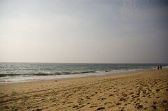 Een verlaten strand op de oceaan waar een bejaard paar in de afstand bij zonsondergang loopt stock foto