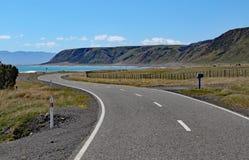 Een verlaten wegwinden naar de baai bij Kaap Palliser, het Noorden, Eiland, Nieuw Zeeland royalty-vrije stock afbeeldingen