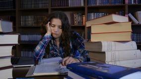 Een vermoeide student treft voor examens in de bibliotheek voorbereidingen 4K stock footage