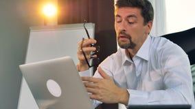 Een vermoeide zakenmantypes op laptop stock footage
