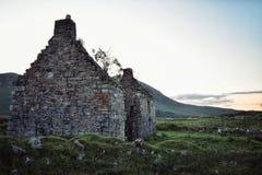 Een vernietigd verlaten steenhuis op een gebied stock foto