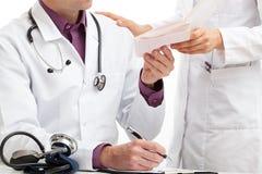 Een verpleegster die bloedonderzoek geven vloeit voor een arts voort stock fotografie