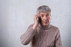 Een verrast bejaarde in sweater die grijs haar om donkere ogen en rimpels op zijn gezicht hebben die over de telefoon communicere royalty-vrije stock afbeeldingen