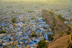 Een verre mening van dicht samengeperste blauwe geschilderde huizen met bomen en heuvels royalty-vrije stock foto