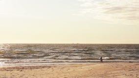 Een verre mening van een jong meisje in een witte kleding die heen en weer op een zandig strand lopen die iets zoeken stock video