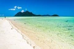 Een verre mens die langs het witte zandige strand op een diepe blauwe hemel langs ver eiland wandelen Royalty-vrije Stock Foto