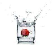 Een vers aardbei bespattend water in een glas op wit Stock Foto's