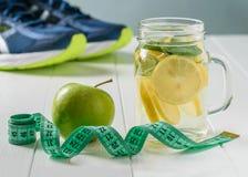 Een vers voorbereide die drank van citroen en munt wordt gemaakt en appel op een witte lijst en looppastennisschoenen Royalty-vrije Stock Afbeeldingen
