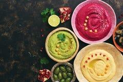 Een verscheidenheid van gekleurde vegetarische hummus, caponata en olijven op een donkere achtergrond, exemplaarruimte De hoogste royalty-vrije stock foto