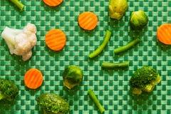 Een verscheidenheid van gemengde groenten op een groene achtergrond Royalty-vrije Stock Foto's
