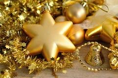 Een verscheidenheid van gouden die decoratie van de Kerstmisboom met gouden klatergoud worden getoond Stock Afbeeldingen