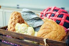 Een verscheidenheid van heerlijke bakkerij, die rond, lang of ovaal is, geplaatst in houten mand Stock Fotografie
