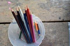 Een verscheidenheid van kleurpotloden in duidelijke plastic dozen stock foto