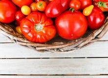 Een verscheidenheid van tomaten in een mand op lijstbovenkant Royalty-vrije Stock Fotografie