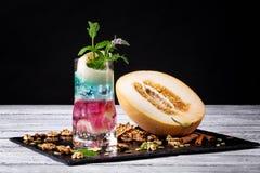Een verse multi-colored alcoholische cocktail naast meloen en verpletterde okkernoten op een zwarte achtergrond De zomerdranken D Stock Fotografie