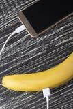 Een verse rijpe banaan wordt verbonden met de touchscreen mobiele telefoon met een witte usbkabel royalty-vrije stock foto's