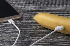 Een verse rijpe banaan wordt verbonden met de touchscreen mobiele telefoon met een witte usbkabel royalty-vrije stock afbeelding
