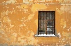 Een versperd venster op de oude gele muur met een snow-covered venstervensterbank royalty-vrije stock fotografie
