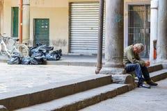 Een verspilde gedronken mens die op de straat sluimeren royalty-vrije stock afbeelding
