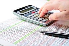 Een verspreidingsblad met pen en calculator. Stock Foto