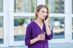 Een in verwarring gebrachte vrouw spreekt op de telefoon Stedelijk concept levensstijl, het werk Stock Afbeeldingen