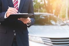 Een verzekerings deskundige werknemer die met een auto bij openlucht werken royalty-vrije stock foto's