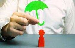 Een verzekeringsagent houdt een groene paraplu over een menselijk cijfer Concept het leven en ziektekostenverzekering Onvoorwaard stock afbeelding