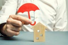 Een verzekeringsagent houdt een rode paraplu over een blokhuis Het concept van de bezitsverzekering Bescherming van huisvesting/h stock afbeeldingen