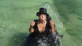 Een vet meisje giet zich met zeewater Langzame Motie stock videobeelden