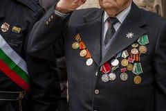 Een veteraan met medailles en orden op het kostuum wordt verfraaid geeft eer tijdens een parade die royalty-vrije stock foto's