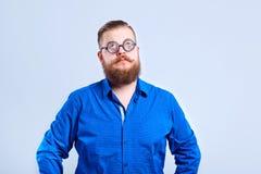 Een vette, gebaarde mens slim met glazen met een slimme stomme expr royalty-vrije stock afbeeldingen