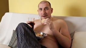 Een vette, kale, luie mens eet chips en drinkt kola, zittend op de laag zonder bovenkleding Dunne mens schadelijk stock footage