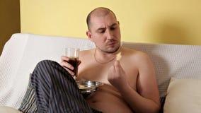 Een vette, kale, luie mens eet chips en drinkt kola, zittend op de laag zonder bovenkleding Dunne mens schadelijk stock video