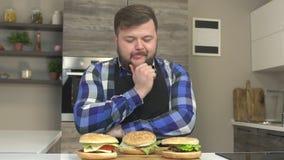 Een vette Kaukasische mens met een baard zit in de keuken en likkend, voor hem zijn drie heerlijke hamburegres stock videobeelden