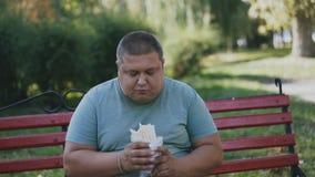Een vette mens eet en bekijkt zijn schadelijk en smakelijk snel voedsel op een bank stock footage