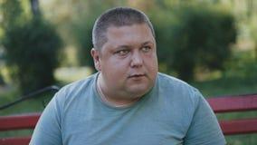 Een vette mens eet schadelijke snel voedsel en dranken coffe op een bank in het park stock footage