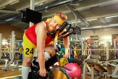 Een vette mens is vermoeid op een simulator in de gymnastiek royalty-vrije stock afbeeldingen